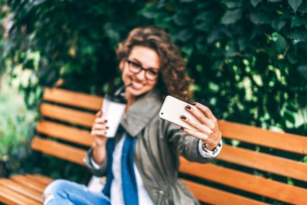 Chica con café rizado bebe café y usa smartphone al aire libre