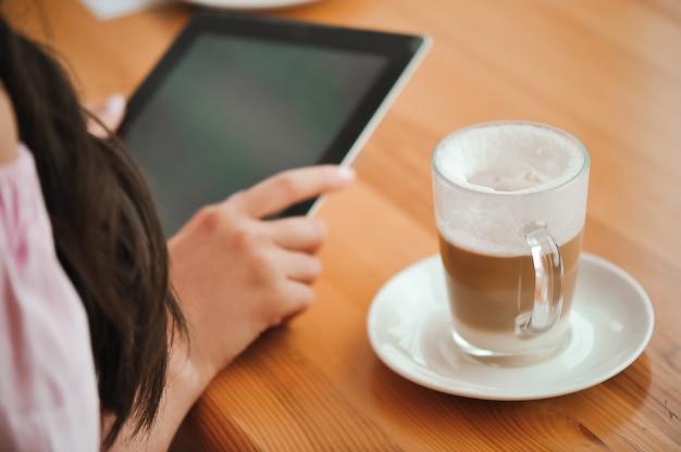 Chica en café utiliza pequeña computadora móvil.