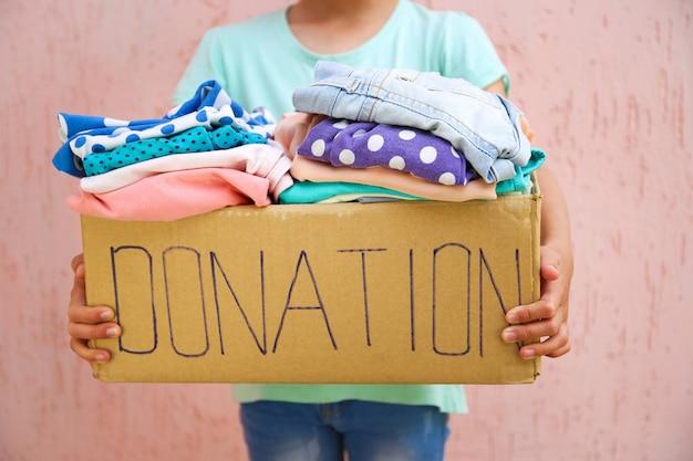Chica con caja de donación con ropa de verano.