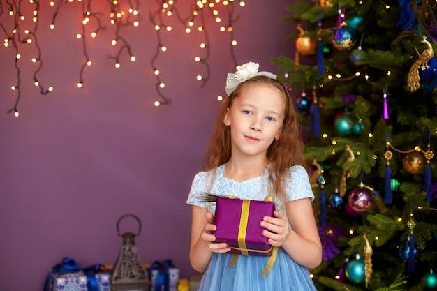 Chica con caja de regalo cerca de árbol de navidad