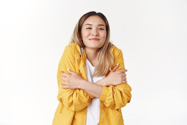 Chica calentando se puso la chaqueta amarilla sensación de frío caminar por la noche verano playa vacaciones abrazándose a sí misma apretada sonriendo encantada mirada satisfecha alegre de pie pared blanca complacida