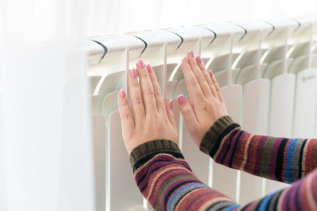 Chica calienta las manos congeladas sobre el radiador caliente, vista cercana