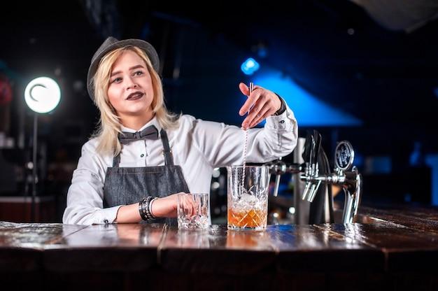 Chica camarera prepara un cóctel en la cervecería