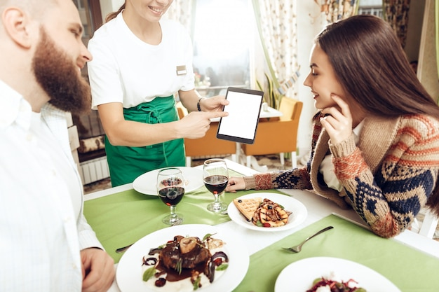 Chica camarera toma un pedido de una pareja joven
