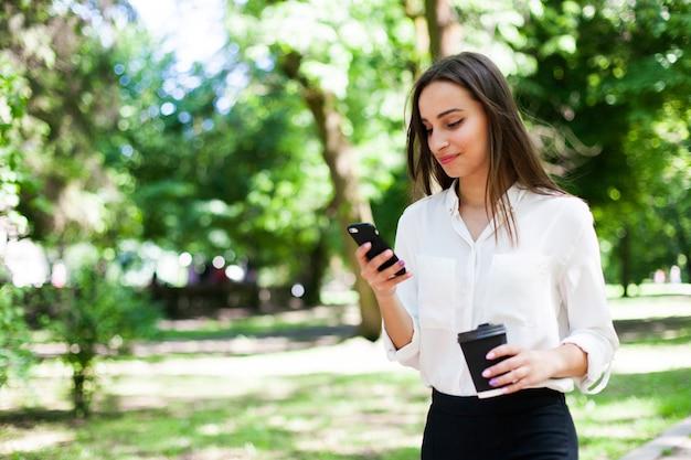 Chica camina con teléfono en la mano y una taza de café en el parque
