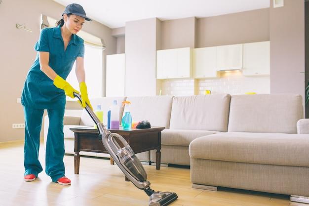Chica está caminando en el apartamento estudio y limpieza de piso con aspiradora. ella lo sostiene con ambas manos. la mujer esta sola.