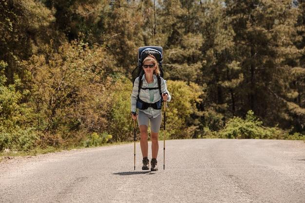 Chica caminando en el camino con mochila de senderismo y bastones de senderismo