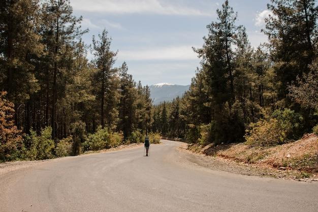 Chica caminando en el camino con mochila de senderismo