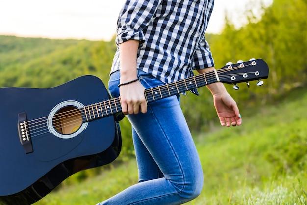 Chica caminando en el campo con una guitarra en la mano