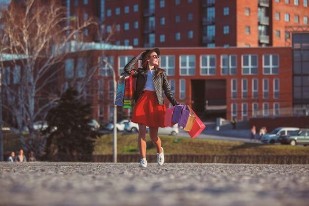 Chica caminando con compras en calles de la ciudad
