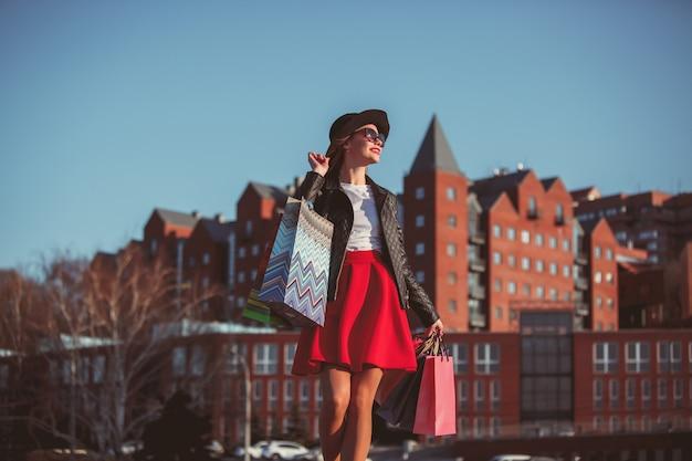 La chica caminando de compras por las calles de la ciudad.