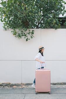 Chica caminando con equipaje en la calle