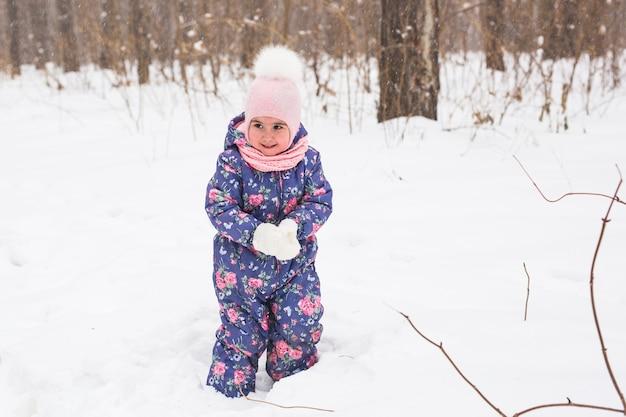 Chica caminando en el invierno al aire libre y tirando la nieve