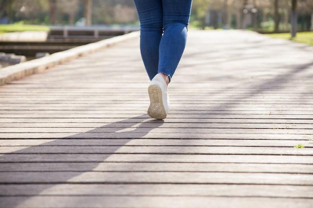 Chica caminando por el sendero en el parque de la ciudad