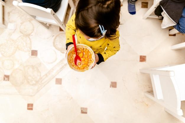 Chica caminando con un tazón de estofado en el comedor de su guardería