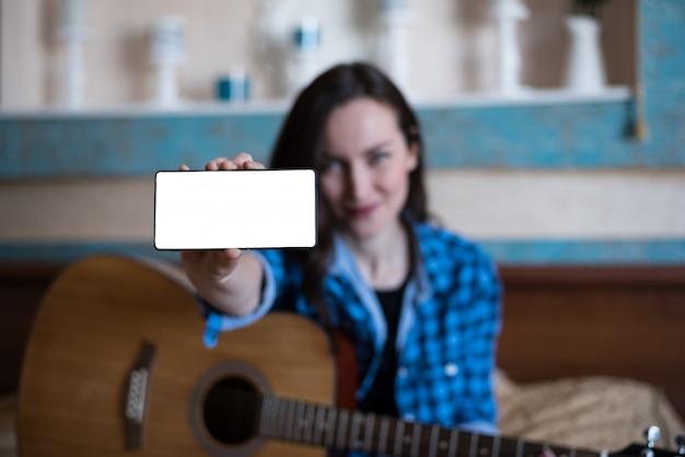 Chica de camisa azul y jeans con guitarra acústica muestra mano con smartphone.