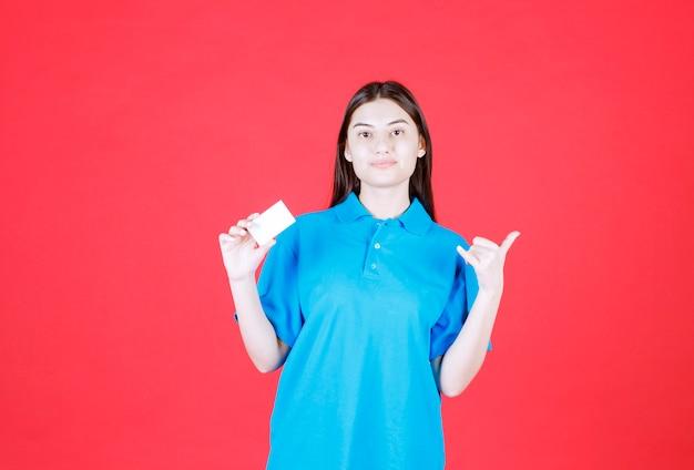Chica con camisa azul presentando su tarjeta de visita y apuntando a su colega alrededor