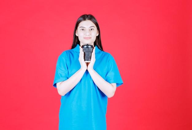 Chica en camisa azul sosteniendo una taza de café desechable negra
