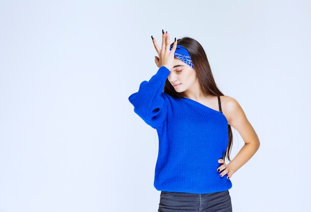 La chica con camisa azul se ve estresada y nerviosa.