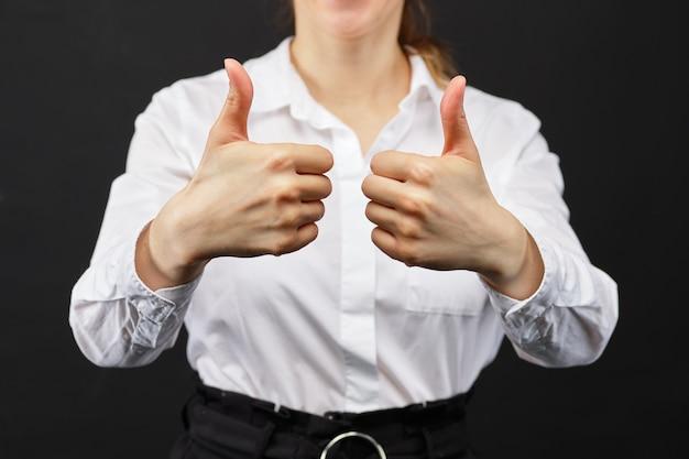 Chica en una camisa blanca pulgares arriba muestra sobre un fondo negro.