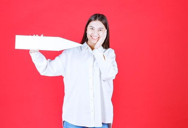 Chica con camisa blanca sosteniendo una flecha apuntando hacia la derecha y parece confundida o pensativa