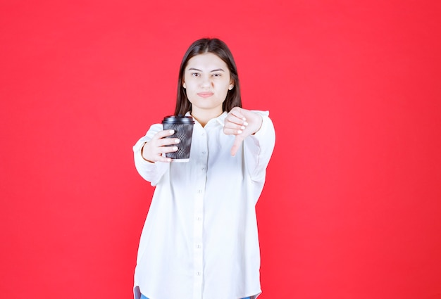 Chica con camisa blanca sosteniendo una taza de café para llevar negra y mostrando el pulgar hacia abajo