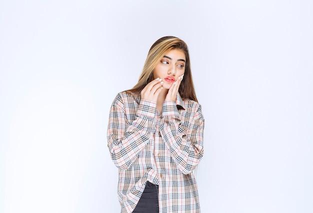 Chica en camisa a cuadros parece pensativa y dudosa