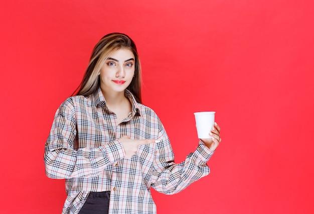 Chica en camisa de cuadros sosteniendo una taza de café desechable blanca