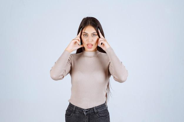 Chica en camisa gris apuntando su cabeza y pensando.