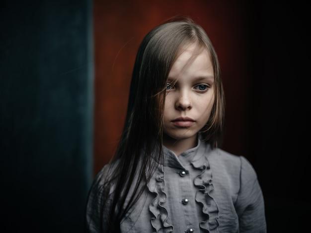 Chica en camisa gris posando emociones de estudio de primer plano