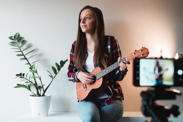 Chica con camisa y jeans escribe un vlog en el teléfono sobre tocar el ukelele.
