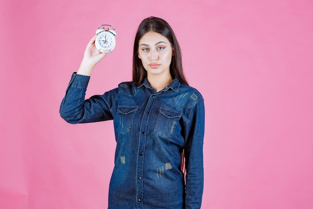 Chica en camisa de mezclilla sosteniendo y promocionando un despertador