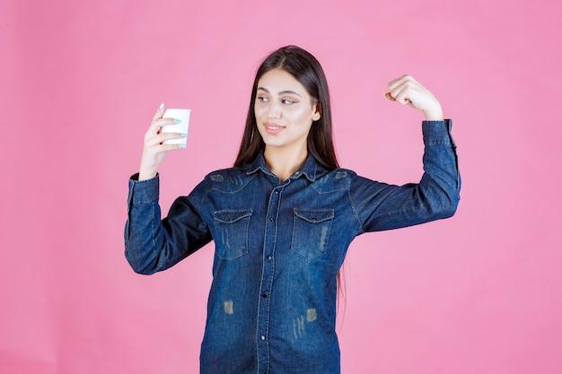 Chica en camisa de mezclilla tomando una taza de café y sintiéndose poderosa
