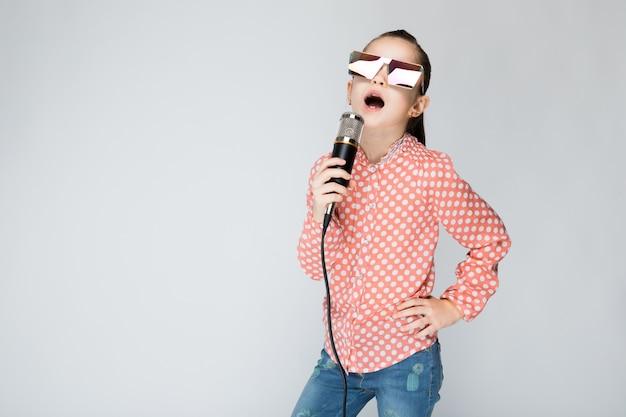 Chica en camisa naranja, gafas y blue jeans en gris