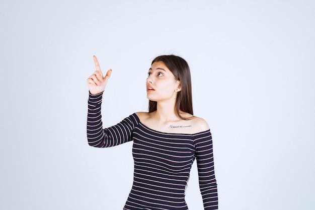 Chica en camisa a rayas apuntando hacia arriba y mostrando emociones.