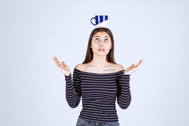 Chica en camisa a rayas poniendo la taza de café en la cabeza.