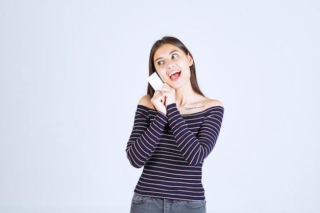 Chica en camisa a rayas presentando su tarjeta de visita con confianza.
