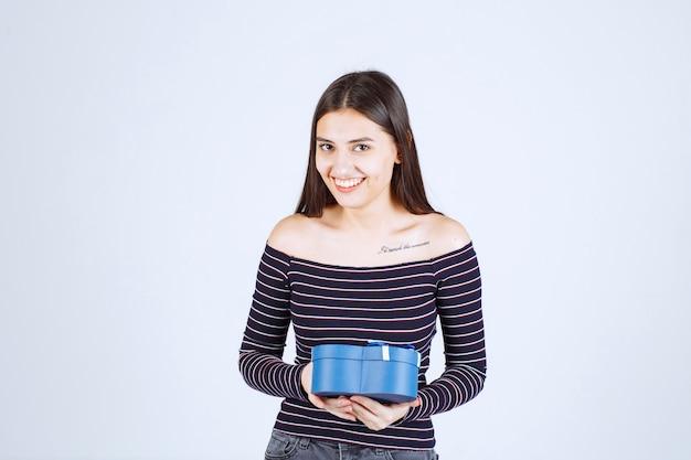 Chica en camisa a rayas sosteniendo una caja de regalo en forma de corazón azul y sonriendo.