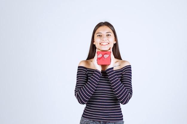 Chica en camisa a rayas sosteniendo una caja de regalo roja y mirando emocionada.