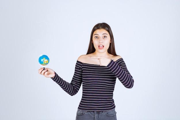 Chica en camisa a rayas sosteniendo un mini globo y apuntando a él.