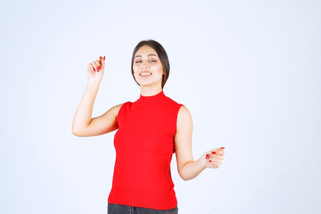 Chica en camisa roja dando poses neutrales, positivas y atractivas.