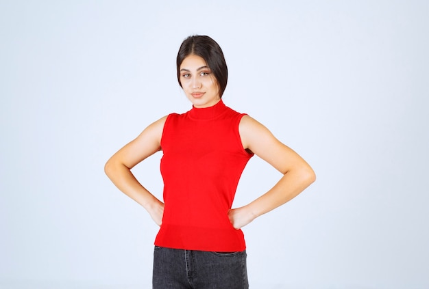 Chica en camisa roja haciendo cara molesta y aburrida.