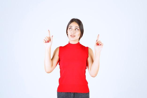 Chica de camisa roja levantando la mano y apuntando hacia arriba.