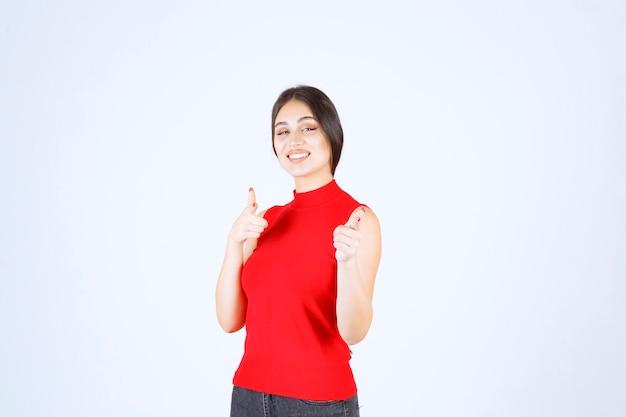 Chica en camisa roja notando a alguien adelante y saludándolo.