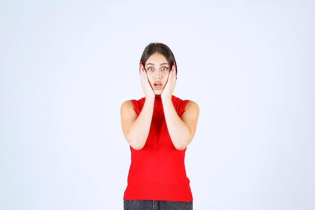 La chica con una camisa roja parece asustada y aterrorizada.