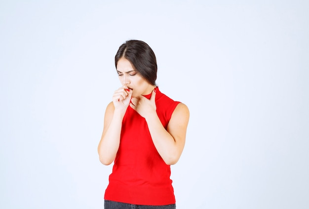 Chica con camisa roja se siente fría y enferma.
