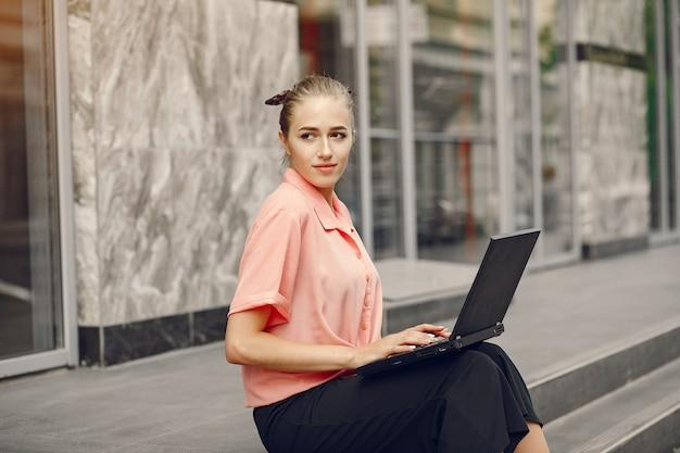 Chica en una camisa rosa sentada cerca de casa y usar la computadora portátil
