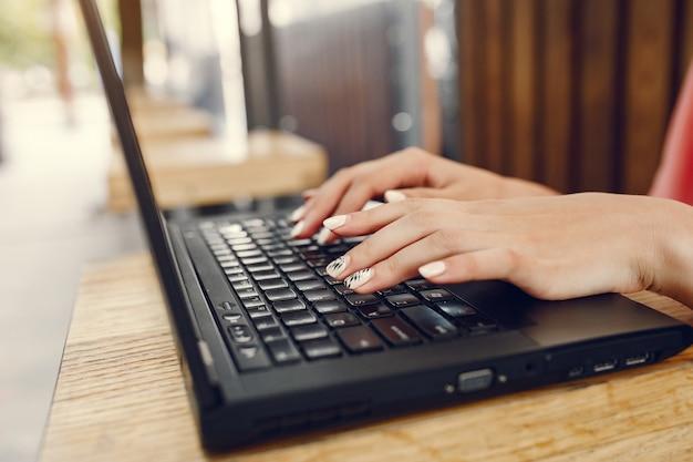 Chica en una camisa rosa sentada en la mesa y usa la computadora portátil
