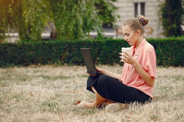 Chica en una camisa rosa sentada en un parke y usa la computadora portátil