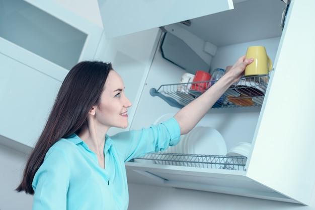 Chica con una camisa turquesa pone una taza amarilla en el estante de secado del armario de la cocina